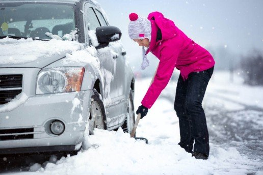 woman shoveling snow from her car