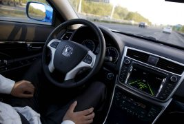 Li, a development engineer at Changan Automobile, removes his hands from the steering wheel while the car is on self-driving mode during a test drive on a highway in Beijing