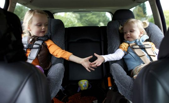 Caucasian sisters holding hands in back seat of car
