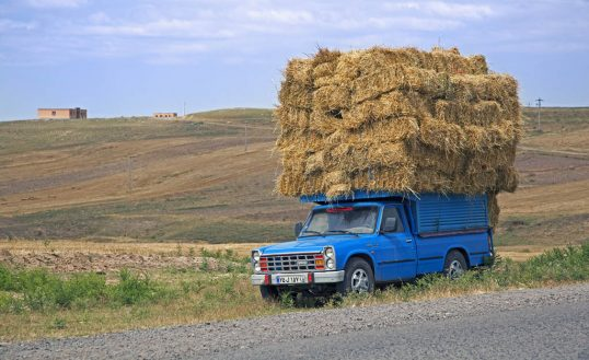 Blue pickup truck heavily loaded with hay bales in rural Iran