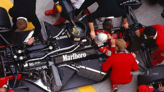 alain-prost-sits-in-his-mclaren-mp4-3-tag-porsche-while-the-mechanics-get-to-work-on-the-car-and-refuel